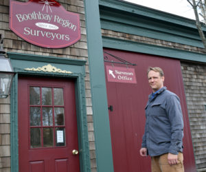 Nicholas Plumer outside the office of Boothbay Region Surveyors at the old town garage in Boothbay. Plumer, of Bristol, bought the long-standing business in 2017 and recently changed the name. (Evan Houk photo)