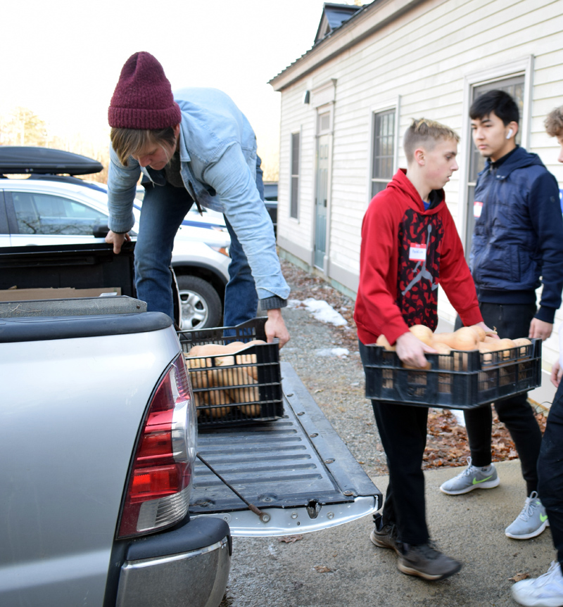 Student volunteers help Kaitlyn Gardner (left), assistant farm manager for Twin Villages Foodbank Farm, unload butternut squash at St. Patrick's Church in Newcastle on Monday, Nov. 25. (Evan Houk photo)