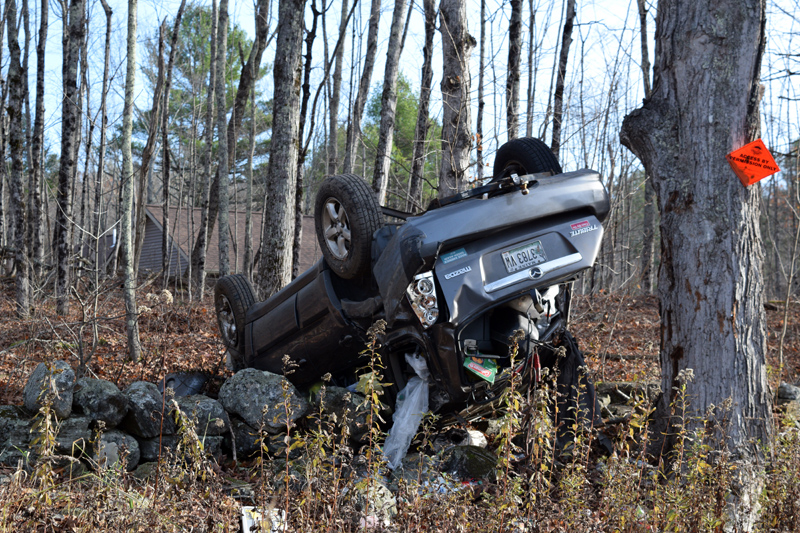 A 2006 Mazda Tribute lies on its roof on a stone wall in Dresden on Monday, Nov. 4. The driver and passenger were treated and released at Maine Medical Center in Portland, according to the hospital. (Jessica C?lifford photo)