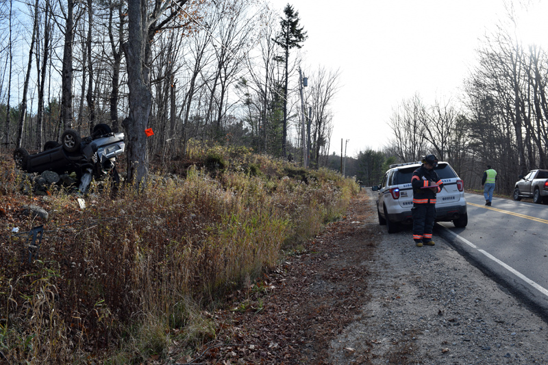 Emergency personnel respond to a rollover on Middle Road in Dresden on Monday, Nov. 4. The vehicle is at rest on a stone wall at left. (Jessica Clifford photo)