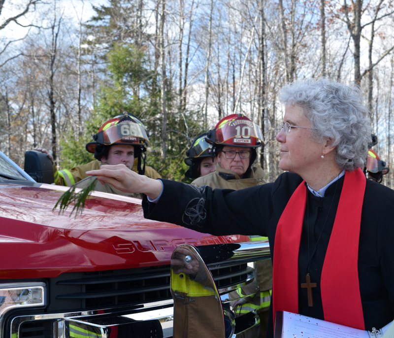 The Rev. Katherine Pinkham, chaplain of the Edgecomb Fire Department, blesses Squad 4 with a pine branch and water as firefighters look on during a ceremony at the station Sunday, Nov. 3. (Jessica Clifford photo)
