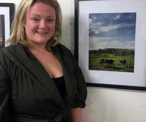 Whitefield photographer Annie Watson poses with one of her photographs of rural life on Friday, Nov. 1 at the opening reception for her exhibit running through the end of November at Sheepscot General in Whitefield. (Christine LaPado-Breglia photo)