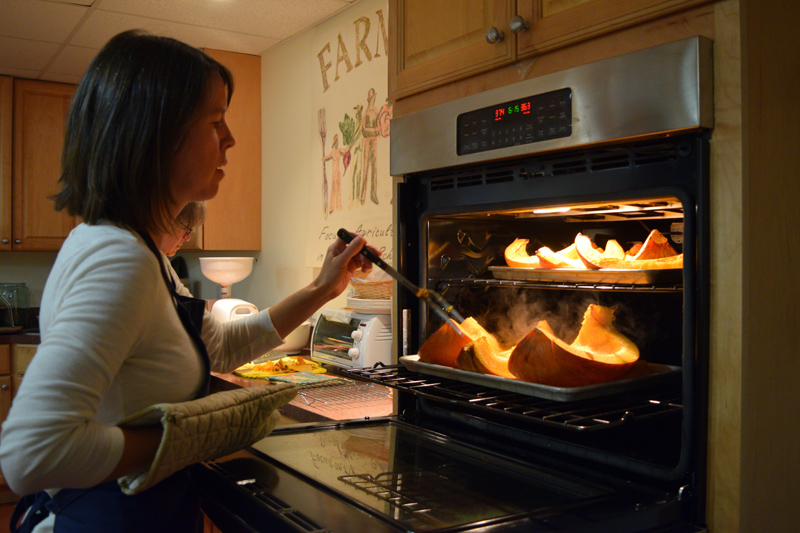 Kate McCarty, food preservation professional with the University of Maine Cooperative Extention, checks on pumpkins in the oven. (Jessica Clifford photo)