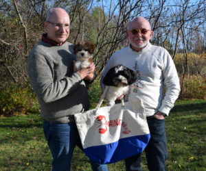 From left: Don Bostick holds Peter and his husband, Danny Cain, holds Milly. Cain is wearing a sweatshirt from their Citizen Maine holiday collection and holding a tote bag from the lobster collection. (Jessica Clifford photo)