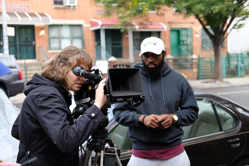 """Hillia Aho with fellow New York University film student Derrick Woodyard on location in New York City. Aho is setting up a film shot as the director of photography for Woodyard's film """"Chalkdust."""" (Photo courtesy Lin Tsung Yen)"""