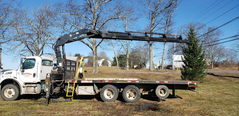 N.C. Hunt Lumber assists with the placement of a tall Christmas tree at Coastal Rivers Conservation Trust in Damariscotta for the Villages of Light celebration.