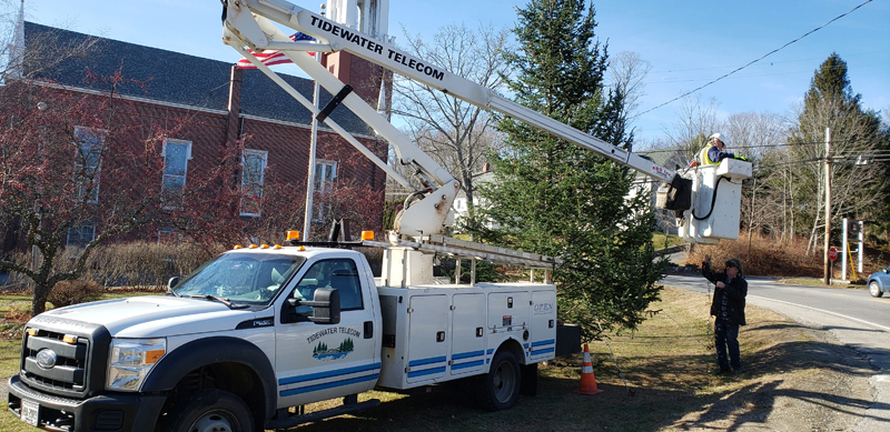 Tidewater Telecom assists with stringing lights on a tall Christmas tree at Veterans Memorial Park in Newcastle for the Villages of Light celebration.