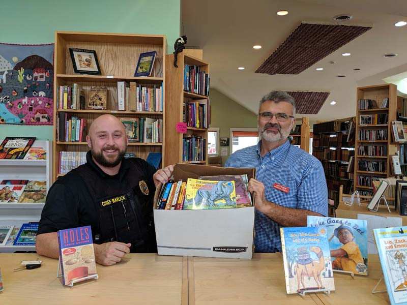 Skidompha Library Executive Director Matthew Graff (right) hands off books from the Skidompha Secondhand Book Shop to Damariscotta Police Chief Jason Warlick.