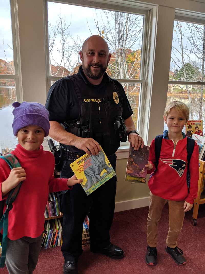 Damariscotta Police Chief Jason Warlick gives books from Skidompha Secondhand Book Shop to Josie and Lucas Branson.