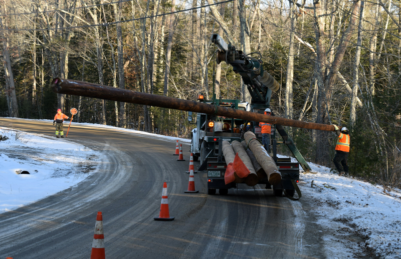 Utility workers install new poles near the former landfill at the corner of Biscay and Standpipe roads in Damariscotta on Dec. 20. A contractor is installing a solar array on the landfill site. (Evan Houk photo)