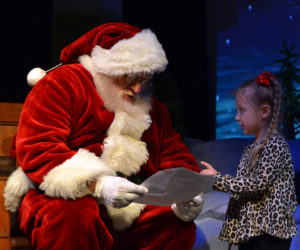 Santa reads a letter from Cali Noriega, 4, of Bristol, during a Villages of Light event at the Lincoln Theater in Damariscotta on Saturday, Nov. 30. (Maia Zewert photo)