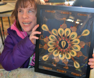 Blind jewelry maker Heather Sprague holds an assemblage piece she made from cast-aside piano parts for the upcoming Mobius Inc. art show at LincolnHealth's Miles Campus. (Christine LaPado-Breglia photo)