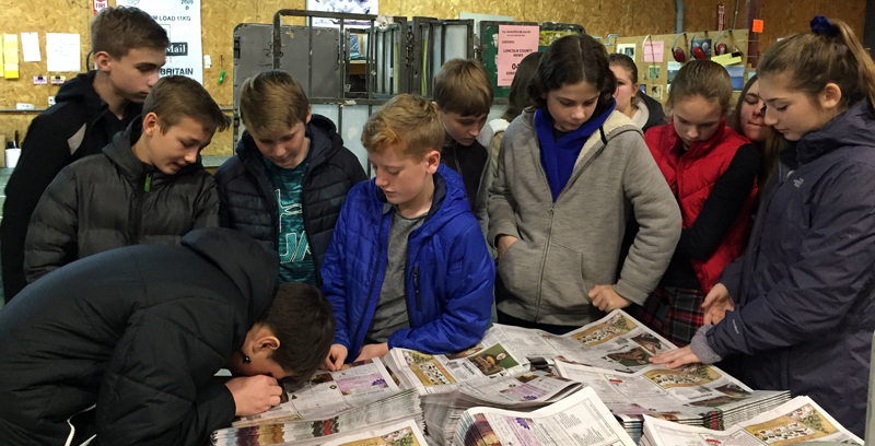 Great Salt Bay Community School eighth graders inspect the print quality of the forthcoming edition of The Lincoln County News during a visit to Lincoln County Publishing Co. in Newcastle on Wednesday, Dec. 11.