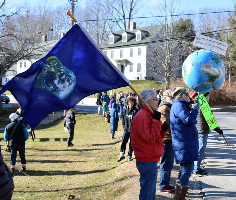 People hold flags, a globe, and signs during a climate change rally at Veterans Memorial Park in Newcastle on Friday, Nov. 29. (Evan Houk photo)