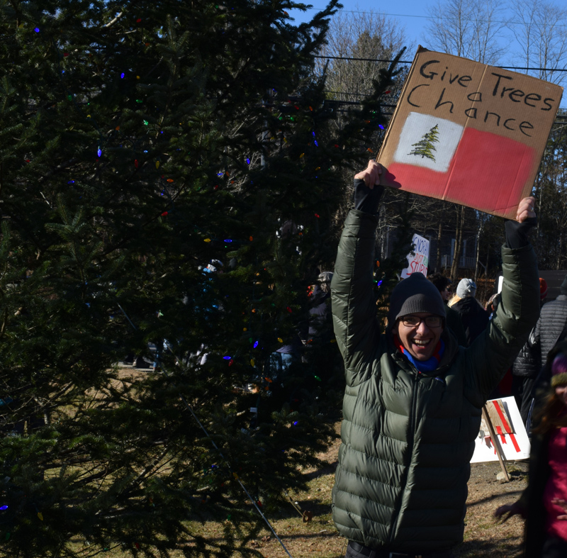 """Mike Lee, of Damariscotta, holds up a homemade sign with the message """"Give trees a chance"""" during a climate change rally at Veterans Memorial Park in Newcastle on Friday, Nov. 29. (Evan Houk photo)"""