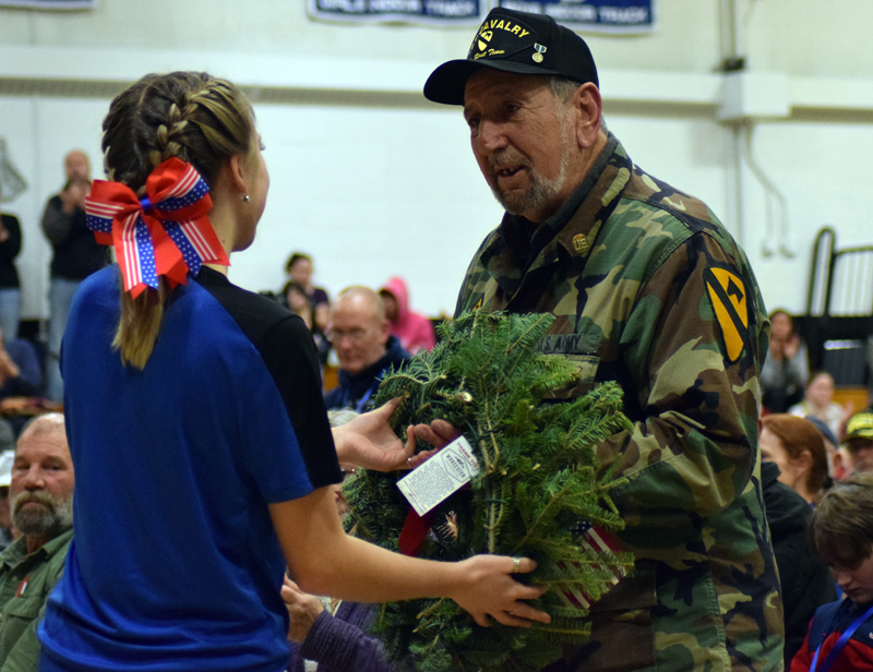 Lincoln Academy student Madison Bradbury presents a wreath to Francis Mortuori, a U.S. Army veteran of the Korean War, during the Wreaths Across America convoy stop at the Newcastle school Sunday, Dec. 8. (Evan Houk photo)