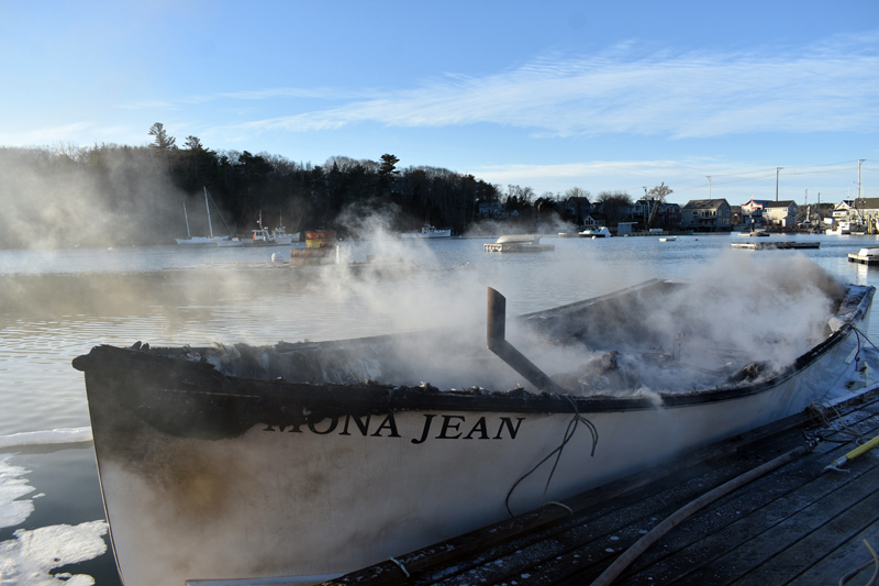 Smoke rises from the remains of the Mona Jean at Eugley Landing in South Bristol on Christmas Eve. The boat caught fire at its mooring and firefighters towed it to the dock. (Alexander Violo photo)