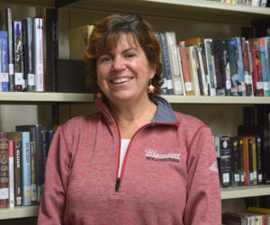 Cynthia Carter, librarian for the Wiscasset School Department, stands in the stacks at the Wiscasset Middle High School library. Carter retired Friday, Dec. 20 after 32 years in Wiscasset schools. (Jessica Clifford photo)