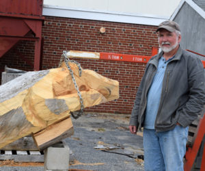 Tony Goulette stands next to a Wolverine sculpture in progress at Wiscasset Middle High School in October. Goulette, a maintenance worker at WMHS, is working with students on the project. (Jessica Clifford photo)