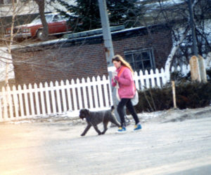 The author at about age 13 walking with her neighbor's dog to deliver newspapers. (Photo courtesy Sarah Caton)