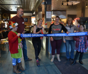 Cupacity owner Susan Murphy cuts a grand opening ribbon in her cafe surrounded by Damariscotta Region Chamber of Commerce board members Wayne Farrin, Terri Herald, and Jane Oliver-Gravel and her daughters Olive and Nolah. (Maia Zewert photo)