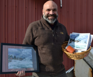 """William """"Billy"""" Smith accepts the 2019 #LCNme365 grand prize during a visit to The Lincoln County News. As the winner of the annual contest, Smith received a prize package of products featuring his photo, including decks of playing cards, postcards, notecards, a framed print, and a 2020 calendar featuring all the monthly winners of the photo contest."""