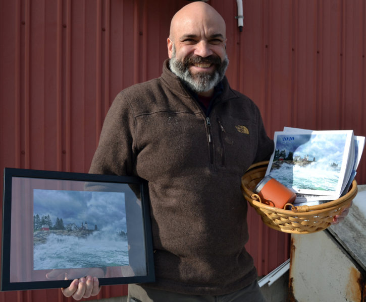 "William ""Billy"" Smith accepts the 2019 #LCNme365 grand prize during a visit to The Lincoln County News. As the winner of the annual contest, Smith received a prize package of products featuring his photo, including decks of playing cards, postcards, notecards, a framed print, and a 2020 calendar featuring all the monthly winners of the photo contest."