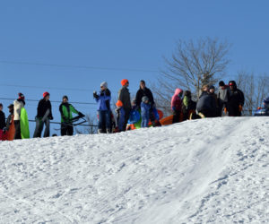 Parents, students, and staff from Bristol Consolidated School watch other sledders brave the hill at Wawenock Golf Club on family fun day, Monday, Jan. 20. The event was part of the WinterKids Winter Games. (Evan Houk photo)
