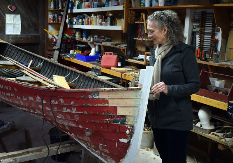 Sonia Turanski, the new executive director at The Carpenter's Boat Shop, inspects a project in the restoration shop. The apprentices at the boat shop learn to build new boats as well as to restore older vessels. (Evan Houk photo)