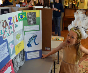 Elizabeth Casad, 8, of Bristol, answers a question about her project on Brazil during Homeschooler Cultural Day at Skidompha Library in Damariscotta on Thursday, Jan. 30. Fourteen homeschooled children from across Lincoln County participated in the event. (Evan Houk photo)