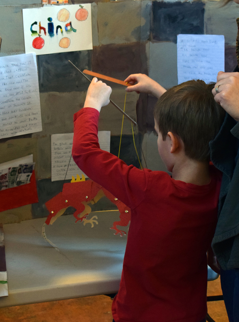 A young boy plays with a prop at the China display during Homeschooler Cultural Day at Skidompha Library in Damariscotta on Thursday, Jan. 30. (Evan Houk photo)