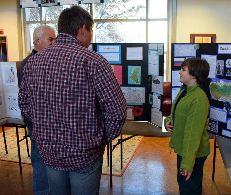Jonah Smith, 11, explains his project on Belgium to visitors during Homeschooler Cultural Day at Skidompha Library in Damariscotta on Thursday, Jan. 30. (Evan Houk photo)