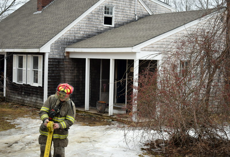 A firefighter rolls up a hose after a kitchen fire at a home in Sheepscot the afternoon of Wednesday, Feb. 26. (Evan Houk photo)