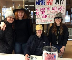 From left: Madison Westrich, Jazzy Bush, Cara Viele, and Kayla Delano staff a donation table in the lobby of Wiscasset Middle High School on hat day, Jan. 24, to raise money for victims of the Australian wildfires. (Photo courtesy Deb Pooler)