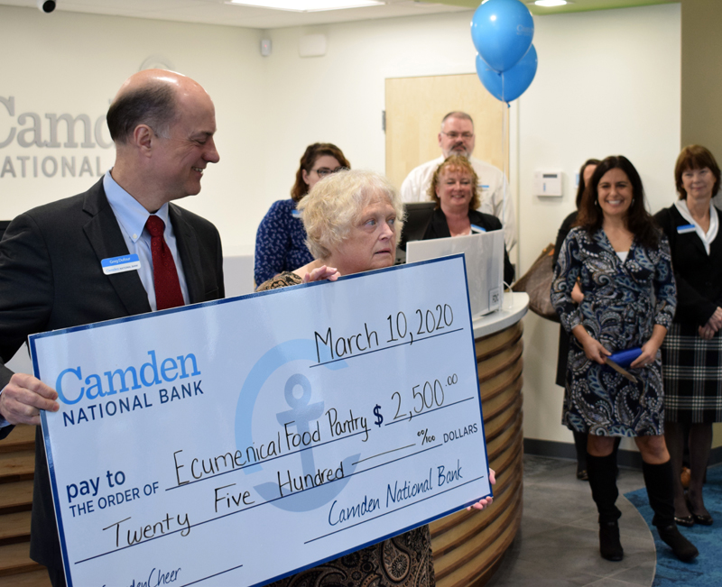 Greg Dufour, president and CEO of Camden National Bank, presents a $2,500 check to Jennifer Ober, president of the Ecumenical Food Pantry, during the grand opening of the bank's new branch in Damariscotta. (Evan Houk photo)