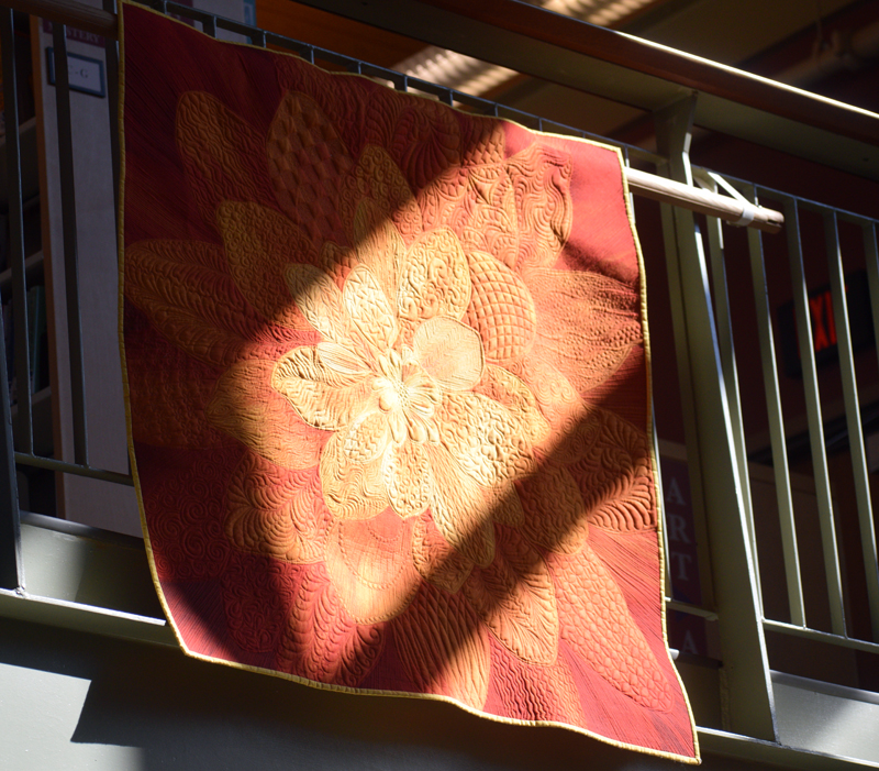 The sun shines on a quilt displayed at Skidompha Library. Deb Boucher, of Edgecomb, created this unnamed quilt and others hanging on the second floor railing of the library. (Jessica Clifford photo)