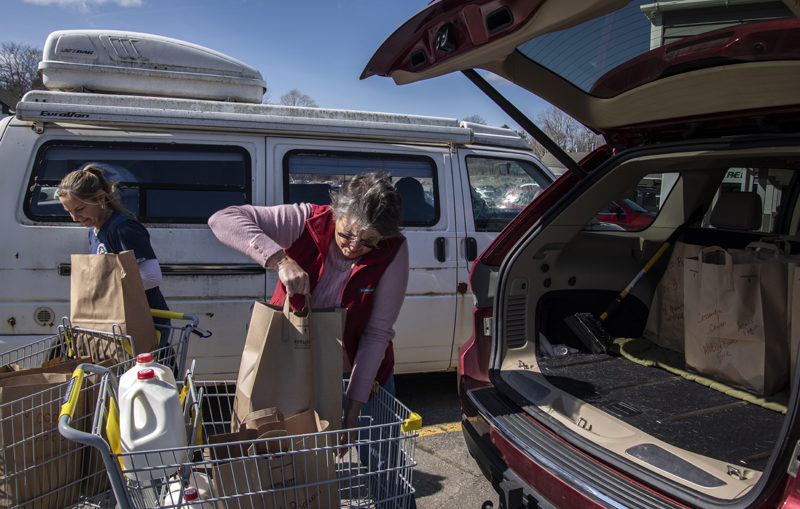 Jane Oliver-Gravel (left) and Robin Mayer load Mayer's vehicle with groceries for delivery to homebound community members Wednesday, March 18. Mayer chairs the Damariscotta Board of Selectmen, while Oliver-Gravel owns Main Street Grocery and coordinates the delivery program. (Bisi Cameron photo)