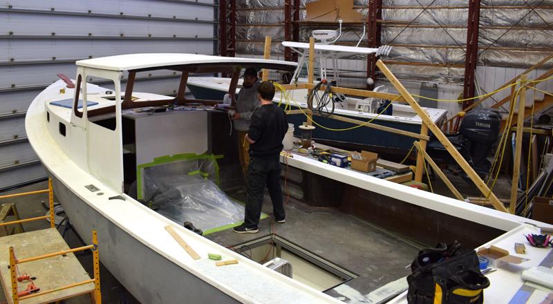 Le constructeur de bateaux principal Dylan Chase et Briland Fisher travaillent sur une nouvelle construction Holland 32 au chantier naval Gamage le 17 février. Le bateau de plaisance sera la première nouvelle construction de Gamage en près de 40 ans. (Photo d'Evan Houk)