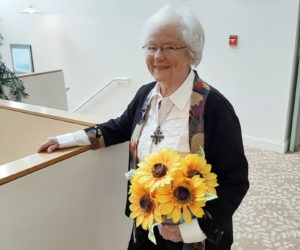 Shirley Tawney is proud of growing up in Kansas. She is pictured here with a sunflower plant. The sunflower is the state flower of her home state.