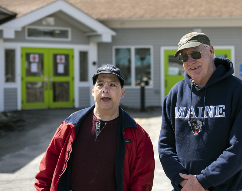 Shawn Rego (left) stands with Direct Support Professional Ed Kennedy in front of the Mobius Inc. community center in Damariscotta on March 31. Rego is in the habit of going to the center every day and continues to visit the building, despite the closure. (Bisi Cameron Yee photo)