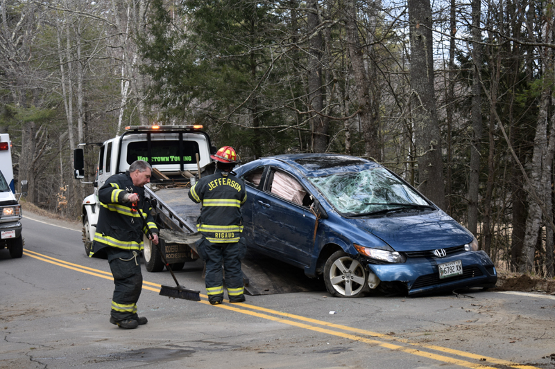 Firefighters sweep debris and help load a vehicle onto a tow truck after a crash on Bunker Hill Road in Jefferson the afternoon of Tuesday, April 7. (Alexander Violo photo)