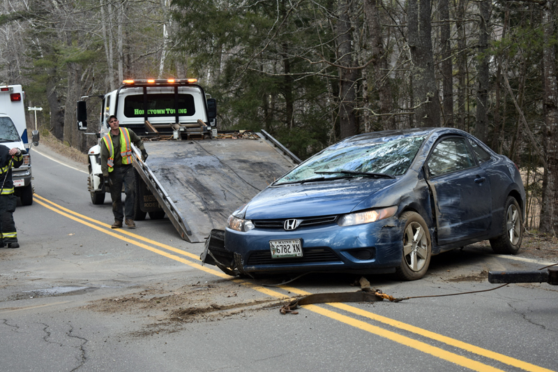 A Honda Civic coupe is removed from Bunker Hill Road in Jefferson after a rollover Tuesday, April 7. The driver suffered unknown injuries, while a passenger was unhurt, according to police. (Alexander Violo photo)