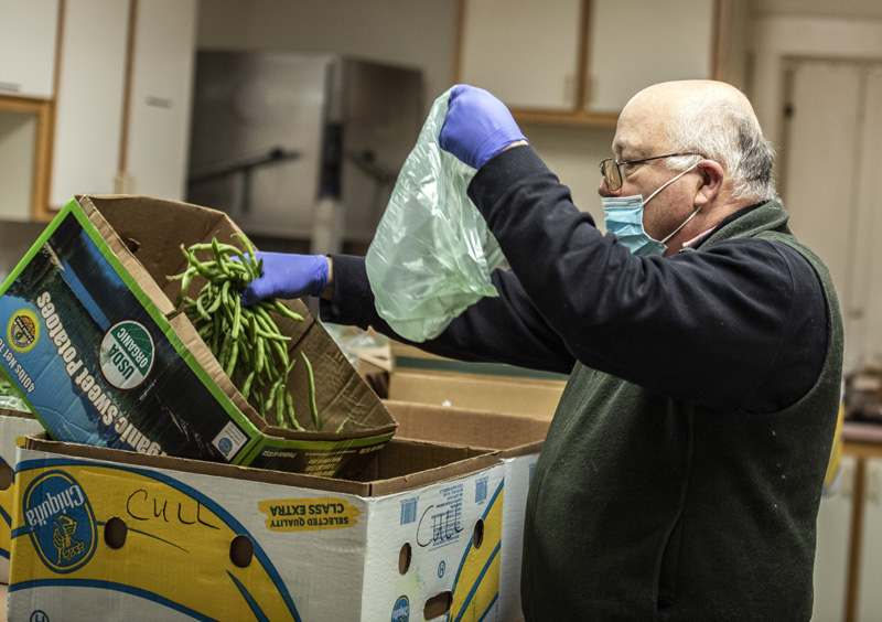 Merle Parise bags green beans at the Ecumenical Food Pantry in Newcastle on Tuesday, April 28. (Bisi Cameron Yee photo)