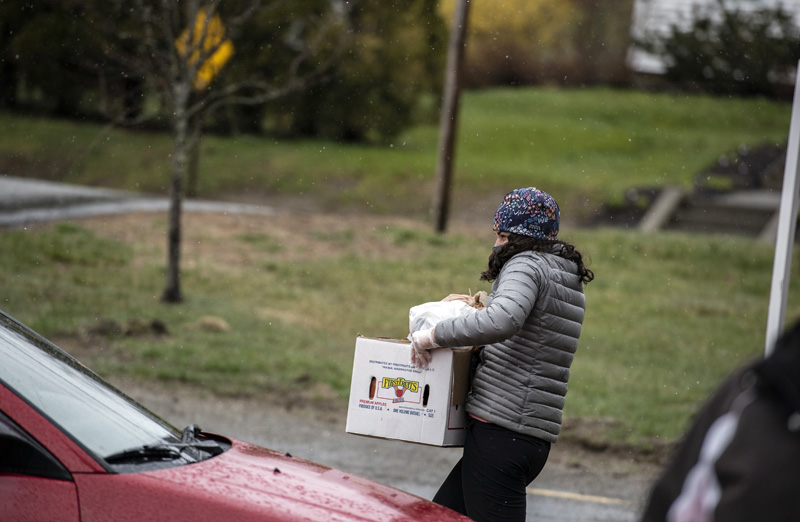 Sam Mengual carries a box of food to a waiting car at the Ecumenical Food Pantry in Newcastle on Tuesday, April 28. Mengual is a lead educator at Camp Kieve in Nobleboro and a volunteer at the pantry. (Bisi Cameron Yee photo)