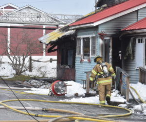 A firefighter works outside Captain's Fresh Idea, on Route 1 in Waldoboro, the afternoon of Easter Sunday, April 12. Fire caused heavy damage to the interior of the building, according to Waldoboro Deputy Fire Chief Dale Smith. (Alexander Violo photo)