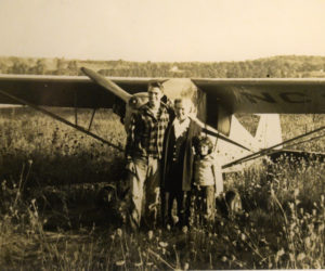 "Billy Post, the pilot; Verlie Greenleaf; and Verlie Greenleaf's granddaughter, Asenath ""Senie"" Greenleaf, pose for a photo after the first plane landing on Westport Island in 1948."