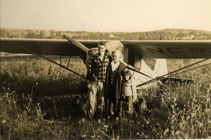 "Billy Post, the pilot; Verlie Greenleaf; and Verlie Greenleaf's granddaughter, Asenath ""Senie"" Greenleaf, pose for a photo after the first plane landing on Westport Island in 1948."