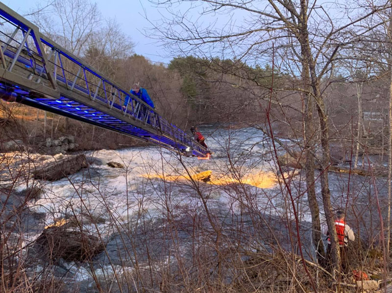 A canoeist climbs a ladder to safety from a rock in the Sheepscot River in Whitefield, Saturday, April 4. Firefighters used a ladder truck to reach two stranded canoeists after their craft broke up in the rapids, according to Whitefield Fire Chief Scott Higgins. (Photo courtesy Whitefield Fire Department)