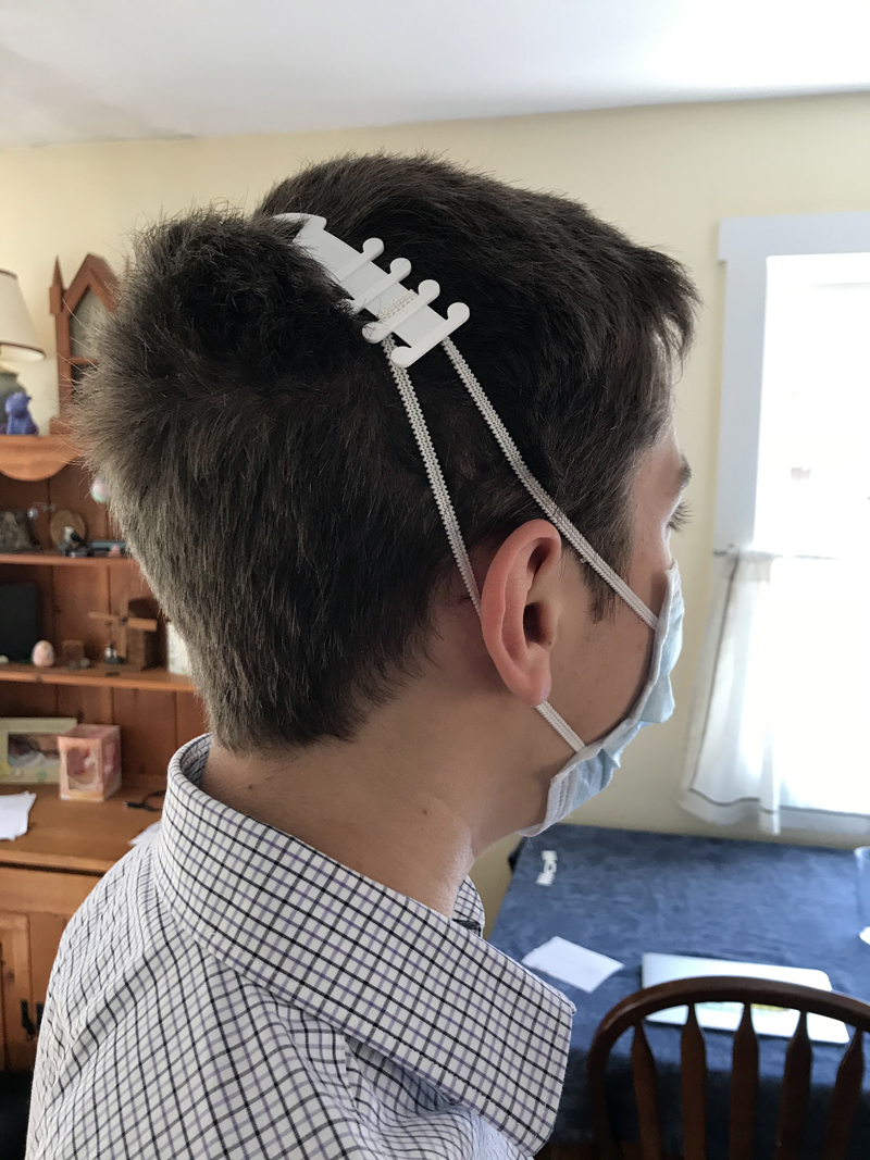 "Sullivan Joyce demonstrates the use of a mask extender, or ""ear saver."" He is making the extenders with his 3D printer and providing them to health care workers and emergency personnel. (Photo courtesy Joyce family)"