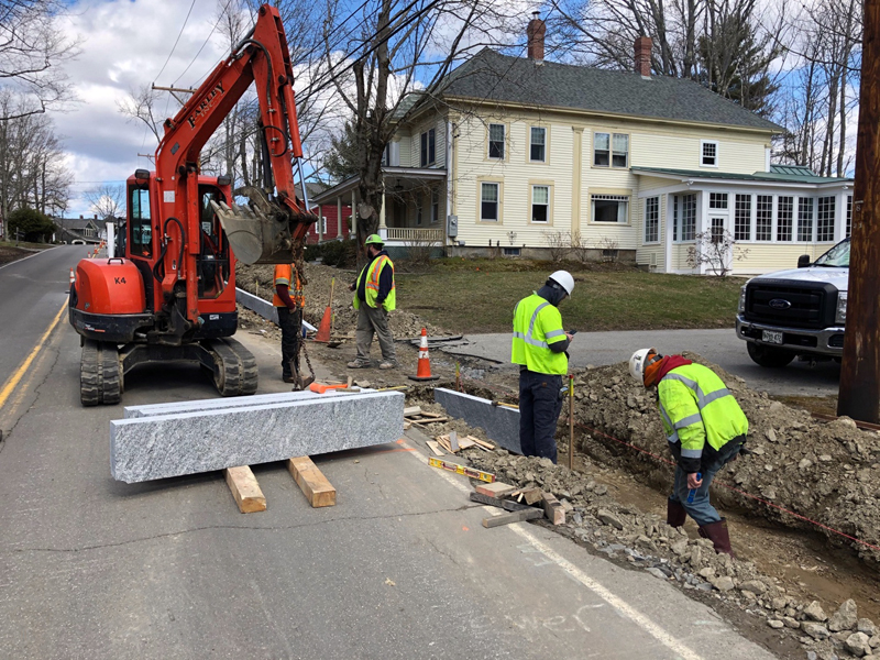 Construction workers install granite curbing on Bristol Road in Damariscotta.